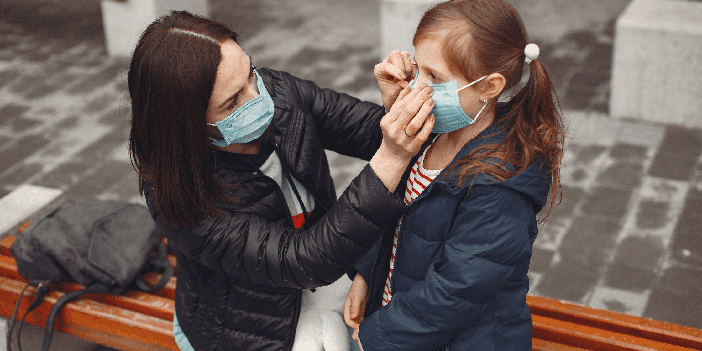 Mother and daughter putting on cloth masks